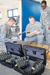 Automated logistical supply specialists from the 21st Theater Sustainment Command's Task Force Harvest (from left) Spc. Brandon Baroncini, Pfc. James Johnston and Sgt. Tu-eisheia Dawson inspect the condition of radios turned in as excess equipment during a property accountability mission at U.S. Army Garrison Baumholder June 10.