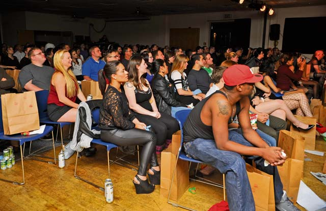 "The audience watches as ""The Rocky Horror Picture Show"" cast acts out the movie during opening night. The audience members received prop bags containing items they were encouraged to use throughout the show, such as rice, hats and squirt guns."
