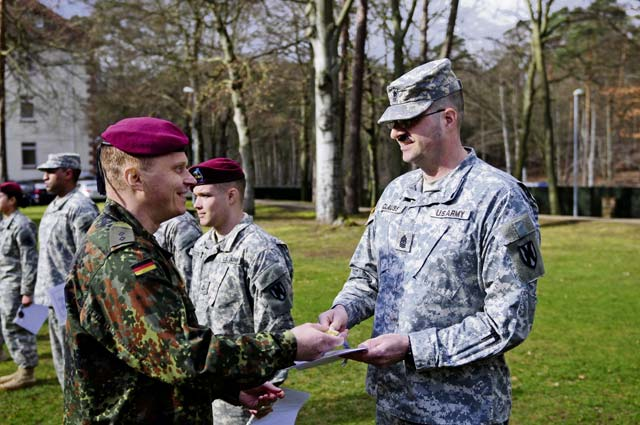 Photo by Brandon BeachFirst Lt. Thomas Gohritz (left), German liaison and company commander with the 263rd Airborne Infantry Battalion, presents a gold Schützenschnur (German Armed Forces Marksmanship Badge) to Sgt. Maj. Michael Clauss, 21st Theater Sustainment Command, Headquarters and Headquarters Company, during an awards ceremony Feb. 21 on Panzer Kaserne in Kaiserslautern. Clauss and 21 other 21st TSC Soldiers earned either gold (highest), silver or bronze decorations for German weapons proficiency. The 21st TSC is U.S. Army in Europe's leading organization for all sustainment activities, including logistics support, transportation, combat sustainment, human resources, finance, contracting and other areas in the field of sustainment. The 21st TSC also serves as the responsible headquarters for USAREUR's military police and engineer brigades, providing combat engineers and military police during partnership training and other operations in support of USAREUR, U.S. Africa Command and U.S. Central Command. The 21st TSC is headquartered in Kaiserslautern.