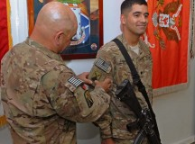 Command Sgt. Maj. Ismael Rodriguez, command sergeant major of Deputy Command Support Operations in Kabul, Afghanistan, presents his son, Spc. Francisco Rodriguez, an information technology specialist from the 580th Signal Company located in Schweinfurt, Germany, with the 7th Signal Brigade combat patch during a ceremony March 26 on Bagram Airfield in Afghanistan.