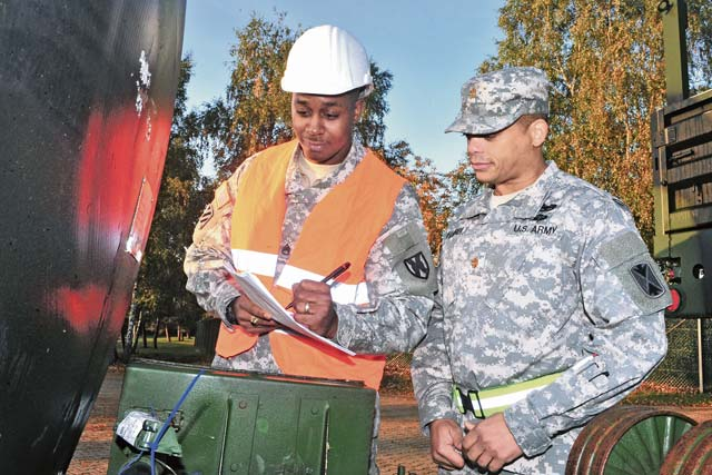 Staff Sgt. Tyler P. Jackson (left), the transportation movement and installation staging area supervisor with the 21st Theater Sustainment Command, reviews a piece of equipment's serial number with Maj. Ernest J. Harrell, the executive officer of the 5th Battalion, 7th Air Defense Artillery, Oct. 18 on Rhine Ordnance Barracks.
