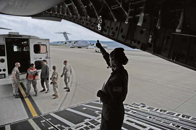 An Airman signals to service members indicating they are able to carry a patient from a Contingency Aeromedical Staging Facility bus Oct. 10 on Ramstein. There isn't a CASF at every base in the Air Force. Depending upon where a medical Airman is stationed will determine whether or not they will work at a CASF.