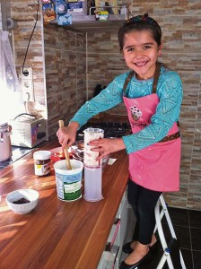 Photo by Celeste MedelAriana Medel, 7, helps her mother in the kitchen.