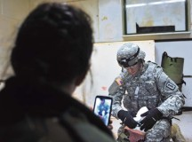 Bulgarian Sgt. Maj. Teodora Kodzhabasheva (left) films Pfc. Travis W. Sinfellow, combat  medic assigned to the 21st Theater Sustainment Command's 557th Medical Company, 421st Multi-Medical Battalion, 30th Medical Brigade, while he applies a bandage to the severed limb of a training dummy during a military-to-military training exchange  Feb. 11 on Smith Barracks in Baumholder.