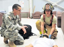 Spc. Thomas P. Shields (left), medic with the 21st Theater Sustainment Command's 557th Medical Company, 421st Multifunction Medical Battalion, 30th Medical Brigade, and Pfc. Michael L. Warren, firefighter with the 513th Firefighting Detachment, 20th Engineer Brigade, render first aid to a simulated casualty during an active-shooter exercise March 20 on Mihail Kogalniceanu Air Base, Romania.