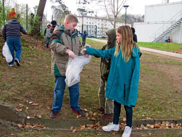 Photo by Debra Crenshaw From left, Vogelweh Elementary School fourth-graders Jacob Queen, Logan Cooper and Ashley Bronner do their part during an Earth Day clean-up drive around the school.