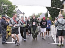 Photo by Bernd MaiStaff Sgt. Derek Hillmer, 720th Explosive Ordnance Disposal Company, crosses the finish line wearing a 75-pound bomb suit during Baumholder's 9/11 Remembrance Run Sept. 11.