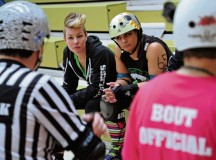 Team members listen to the bout official for rules and restrictions.