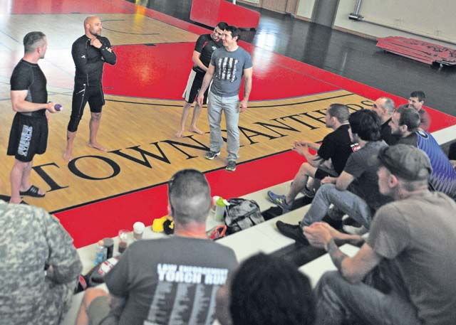 "From left, mixed martial arts fighters Marcus ""The Irish Hand Grenade"" Davis, Frank Trigg, Cole ""The Apache Kid"" Escovedo and Tim Kennedy talk to members of the KMC about their backgrounds during the Armed Forces Entertainment 2014 MMA All-Stars Summer Tour June 19 on Kleber Kaserne."