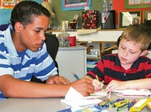 Courtesy photoBrice Relaford, Ramstein High School Deployment Buddies mentor, helps a Ramstein Elementary School student draw a card for his father Jan. 29 on Ramstein. High school and elementary school students of deployed service members come together once a month to share experiences and provide comfort to one another through the Deployment Buddies Program during their parent's deployments.