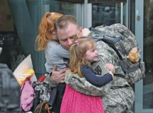 Maj. Gavin Luher, disbursing officer with the 21st Theater Sustainment Command's 266th Financial Management Support Center, is greeted by his family Oct. 7 after returning from a nine-month deployment to Kuwait.
