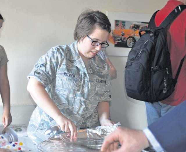 Photo by Kimberly Parker  Airman 1st Class Macey Walker, 786th Force Support Squadron evaluations tech, helps set up dinner, which was provided by the Chief's Group, July 25 at Club 7 on Ramstein. Different organizations rotate cooking dinner for Club 7 every Friday evening.