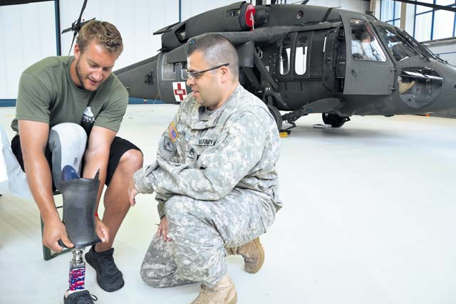 Photo  by Rick Scavetta Max Rohn, a Navy Corpsman who lost a leg in Iraq, shows his prosthetic limb to Army Staff Sgt. Robert Dorris, a flight medic from Company C, 1st Battalion, 214th Aviation Regiment. Severely wounded veterans recently visited Landstuhl to see where they were treated, a trip organized by the Semper Fi Fund.