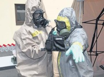 Sgt. Bajram Peci (left), leader decontamination station, 1st Platoon, HAZMAT Company, Civil Protection Regiment, Kosovo Security Force, removes a chemical protection suit from Staff Sgt. Wendell Reeder, survey team chief, 773rd Civil Support Team, 7th Civil Support Command, during a Defense Threat Reduction Agency-sponsored preparedness partnership exercise Aug. 20 on Panzer Kaserne.