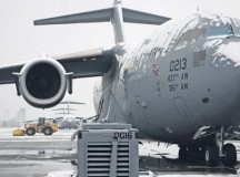 A C-17 Globemaster III sits on the Ramstein flightline Dec. 3 as civil engineers clear the ramp after the first snowfall of the season. The 786th Civil Engineer Squadron heavy equipment shop came in early in the morning to ensure Ramstein can keep launching aircraft.