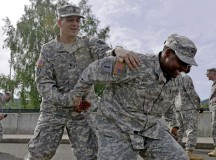 Sgt. Joshua Overton, human resources NCO with the 21st Theater Sustainment Command, practices unarmed self-defense techniques on Staff Sgt. Fredrick Longhorn, HR NCO with the 21st TSC, during guard force training May 21 on Rhine Ordnance Barracks.
