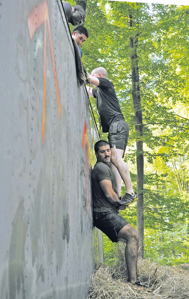 A Mudless Mudder team helps each other over an obstacle. The obstacles consisted of a low-crawl, hay bales, a tightrope, a tire hill and dunk tanks, among others.