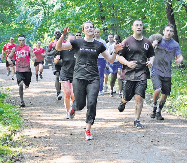 Participants cheer as they run to the next obstacle during the Mudless Mudder June 19 on Ramstein. Participants competed for first, second, third and last places, as well as best costume.