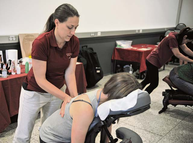 Massage therapist Amber Maez massages a member of Team Ramstein at the Kaiserslautern Military Community Fair Oct. 17 on Ramstein.