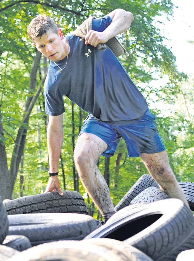 A Mudless Mudder participant climbs over a hill of tires. Each team had to carry a sandbag throughout the course without spilling it.