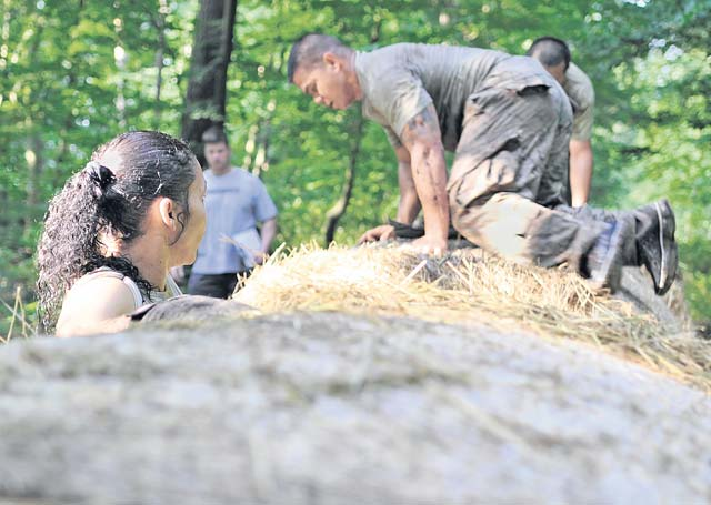 Participants climb over a hay bale obstacle during the Mudless Mudder June 19 on Ramstein. Teams were rated on the amount of time it took to get through the course as well as the number of penalties received during each obstacle.