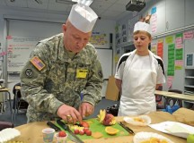 U.S. Army CW2 Bill Michitsch, 10th Army Air and Missile Defense Command G-4 food service technical adviser, shows students at Ramstein Middle School how to attractively garnish fruits and vegetables May 17. The students were part of the Advancement via Individual Determination college preparatory program, which showcases life skills needed to succeed in a variety of careers.