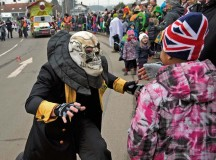 A parade participant interacts with a crowd member during the Fasching parade in Ramstein-Miesenbach.