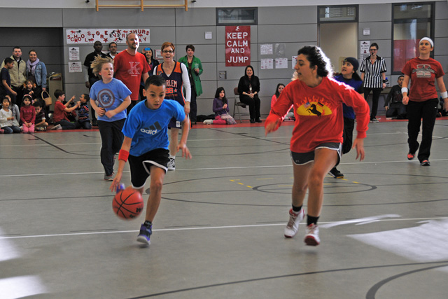 Photo by Heidi BuschStudents vs. staff basketball matchKaiserslautern Elementary School fifth-grader DeShawn Ladipo dribbles the ball past Toni Dailgle during a friendly match of basketball that set KES students against staff members. During the game, which was sponsored by the student council, the fifth-graders beat the staff 18-17 in a last-second shot.