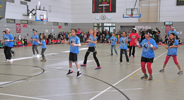 """Photo by Heidi BuschKES is 'Happy'Kaiserslautern Elementary School student council members and their sponsors perform a half time routine to the song """"Happy"""" during the KES students vs. staff basketball match."""