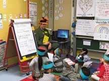 Courtesy photoTech. Sgt. Chris Vanwy, 603rd Air Operations Center, reads to Vogelweh Elementary School students on National Read Across America Day.