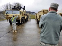 An Air Force officer observes as Soldiers from the 21st Theater Sustainment Command's 240th Quartermaster Company, 18th Combat Sustainment Support Battalion, 16th Sustainment Brigade load a mobile refrigeration unit onto a palletized load system during a professional development session Feb. 26 on Baumholder's Smith Barracks.