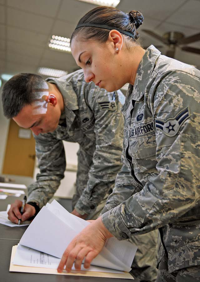 Airman 1st Class Danelle Oliver, 786th Force Support Squadron customer service technician, accepts paperwork from a base newcomer. Upon arrival, one of the first steps they must complete is to be correctly gained into their new units.