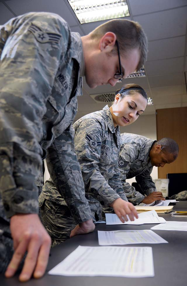 Airman 1st Class Danelle Oliver, 786th Force Support Squadron customer service technician and Tech. Sgt. Dwayne Freeman, 786th FSS  noncommissioned officer in charge of customer support, accepts in-processing paperwork from a base newcomer.