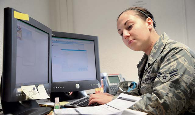 Airman 1st Class Danelle Oliver, 786th Force Support Squadron customer service technician, inputs data from base newcomer in-processing worksheets.