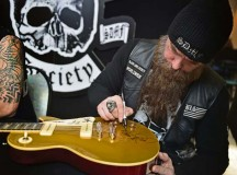 Zakk Wylde, lead vocalist, rhythm guitarist and pianist for the Black Label Society, signs a guitar for an Airman. Wylde, a former guitarist for Ozzy Osbourne, and the band put on a free concert for Team Ramstein with the help of the USO.