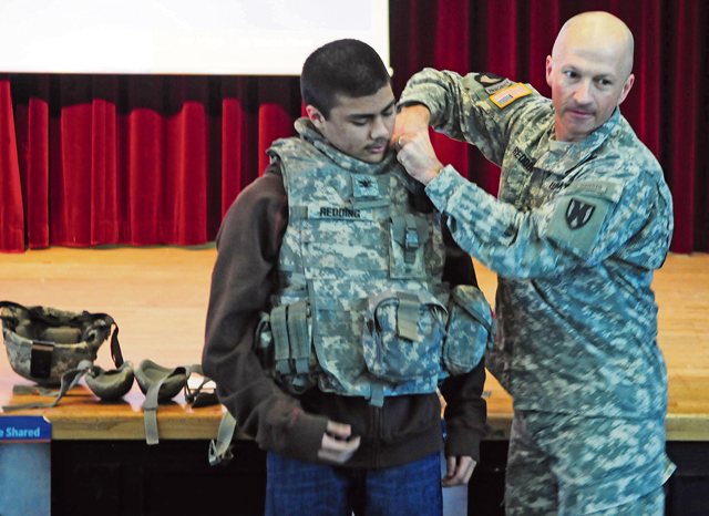 Col. Matthew Redding, 21st Theater Sustainment Command chief of staff, helps a student don military protective armor during the resiliency forum. The chief subsequently directed the student to run across the room and do pushups.