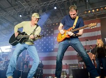 Trace Adkins jams with the lead guitarist in his band during a USO concert for members of the KMC April 20 on Ramstein.