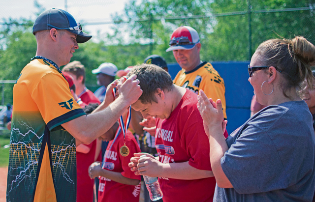 Senior Airman Bryan Painter, a volunteer from the 86th Maintenance Squadron, places a medal around Tyler Simon's neck at the Ramstein High School softball field during the 2nd Annual Adaptive Softball Game.