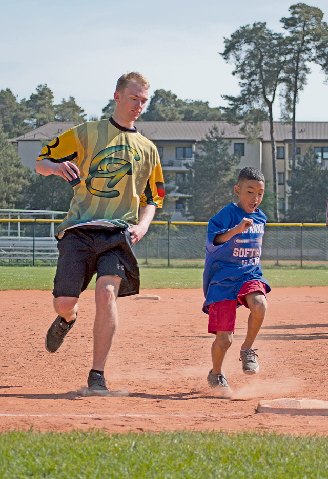 Airman 1st Class Glennon Parks, a volunteer from the 86th Aircraft Maintenance Squadron, runs to third base alongside Elijah Muhammad at the Ramstein High School softball field during the 2nd Annual Adaptive Softball Game May 14 on Ramstein. The event provides an opportunity for special needs children to participate in a healthy activity while receiving recognition for their efforts.