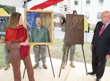 Photo by Rick Scavetta, U.S. Army Garrison Public Affairs Christa Dirgins and retired Gen. Gordon Sullivan unveil a shadowbox, painting and plaque dedicated to the late Brig. Gen. Richard Dirgins April 17 at Daenner Kaserne.