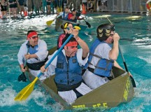 Participants from the 786th Force Support Squadron paddle pass the other teams during the Battle of the Battleships competition May 15 on Ramstein. The competition began with boat races, where teams were tasked to pedal their custom-built boats from one end of the pool to the other as quickly as possible.