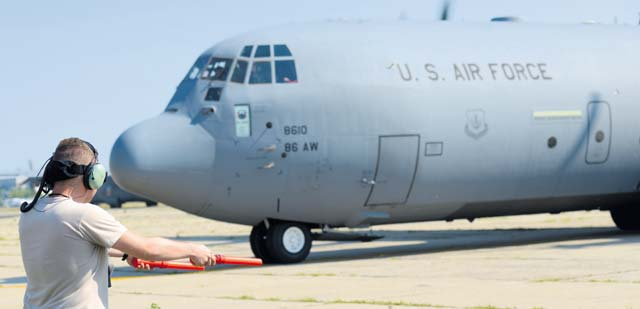 Airman 1st Class Zachary Hitchcock, 37th Airlift Squadron crew chief, marshalls an 86th Airlift Wing C-130J Super Hercules away from its parking spot Aug. 16 at Otopeni Air Base, Romania.