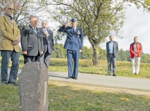 Col. Harry Benham, U.S. Air Forces in Europe Operations and Plans chief, salutes during the playing of taps during the unveiling of a memorial stone for a World War II pilot Sept. 25 in Dietingen, Germany. Second Lt. Priesley Cooper Jr. was conducting an escorting mission when he was shot down.