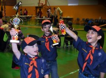 Tiger Cubs Kade Dressing, age 6 (left), Mason McMillan, age 7 (center), and Evan Zawojski,  age 7, celebrate their triumphs in the aftermath of the Pack 69 Pinewood Derby held Jan. 23 at Vogelweh Elementary School. Over 30 cars competed during the annual Scout racing extravaganza. Siblings, parents and adult volunteers as well as Scouts designed, cut and decorated wooden cars for the competition.