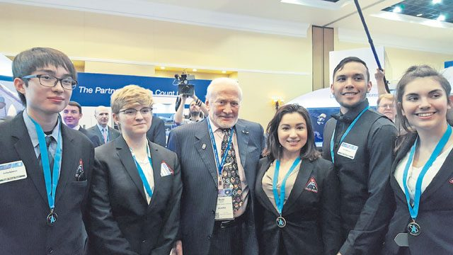 The Kaiserslautern High School StellarXplorers team meets astronaut Buzz Aldrin at the 32nd Space Symposium April 14 in Colorado Springs, Colorado. From left to right: Vincent Povilaitis, junior; Karina Sahli, freshman; Buzz Aldrin; Rhiannon Jimenez, senior; Nathan Throckmorton, senior; and Sandra Mako-Sanchez, junior.