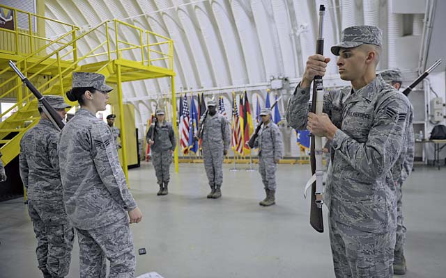 Senior Airman Angelo Hightower, U.S. Air Force Honor Guard Drill Team member, demonstrates the motions to perform a right-shoulder maneuver March 15 on Ramstein. Ramstein Honor Guard members were given the opportunity to learn uniform preparation and color guard motions from U.S. Air Force Honor Guard members.