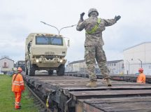 """Sgt. James Gross, 3rd Infantry Division, guides a vehicle into position on a train car at Coleman Work Site, Mannheim, while """"Deutsche Bahn,"""" meaning """"German Rail,"""" members look on."""