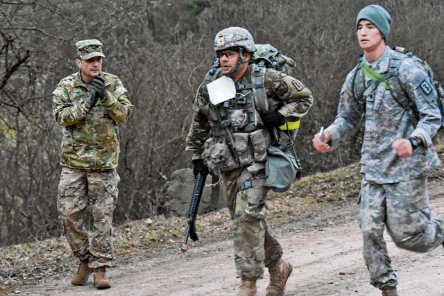 Col. William Stubbs, 30th Medical Brigade commander, cheers on Soliders during a 12-mile ruck march that was part of the U.S. Army Europe Expert Field Medical Badge event March 24 at Baumholder.