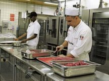 Private 1st Class Kadavius Williams, 21st Theater Sustainment Command food service specialist (left), and a civilian culinary specialist prepare meat for the main-line portion of dinner May 9 at the Clock Tower Cafe on Kleber Kaserne. The Clock Tower Cafe is the 2016 Phillip A. Connelly Department of the Army level Best Garrison Dining Facility.