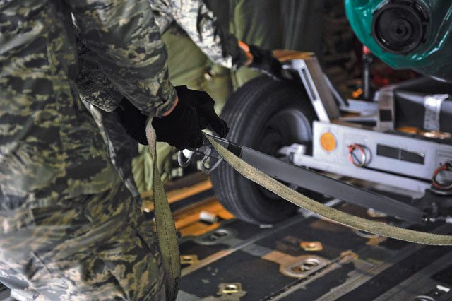 An aircraft maintainer straps down a piece of cargo onboard a C-130J Super Hercules after being loaded in support of Wing Thunder April 22 on Ramstein. The cargo loaded was to test the operational readiness of aircrew during real-world and exercise scenarios.